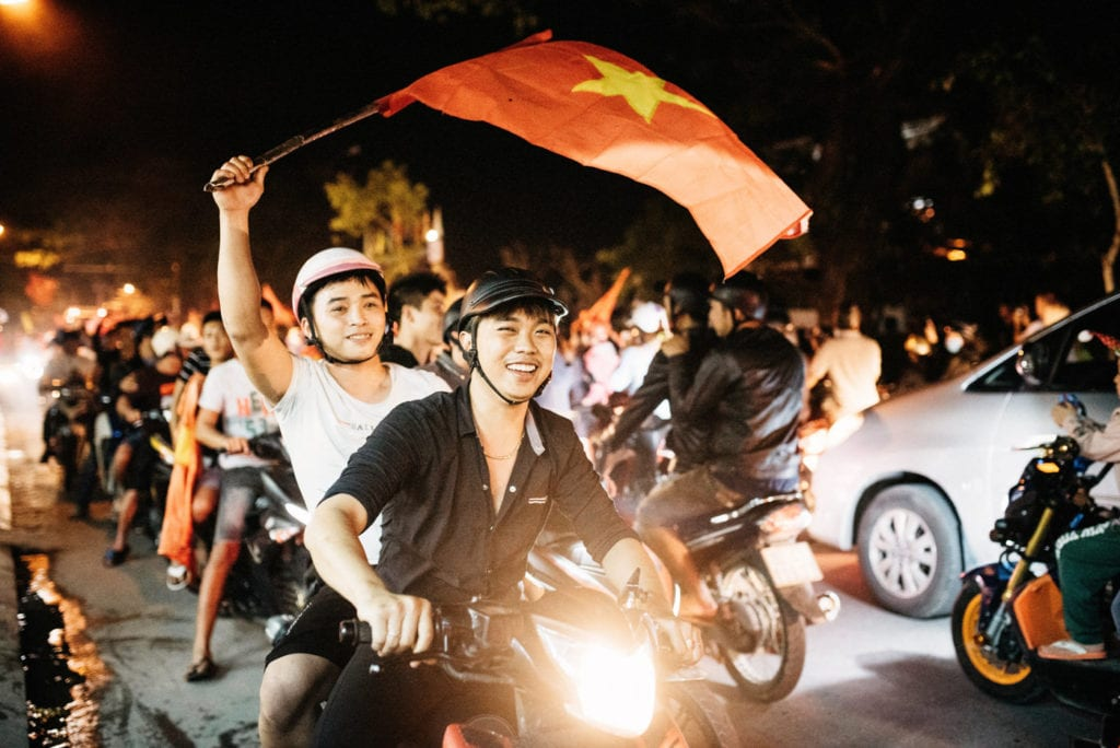 Ho Chi Minh City Guy riding on a scooter with vietnamese flag