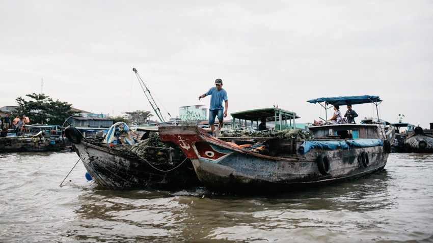 Man hopping between two boats on the Mekong River