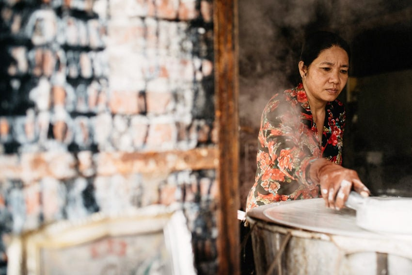 Woman producing fine rice paper by hand