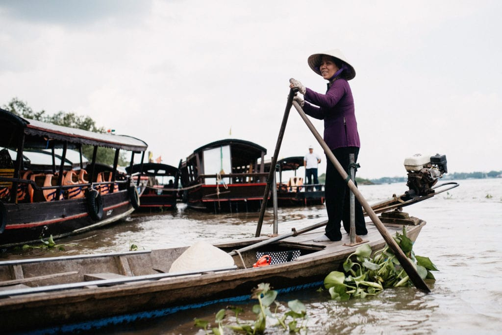 Woman paddling on a small boat in the Mekong Delta